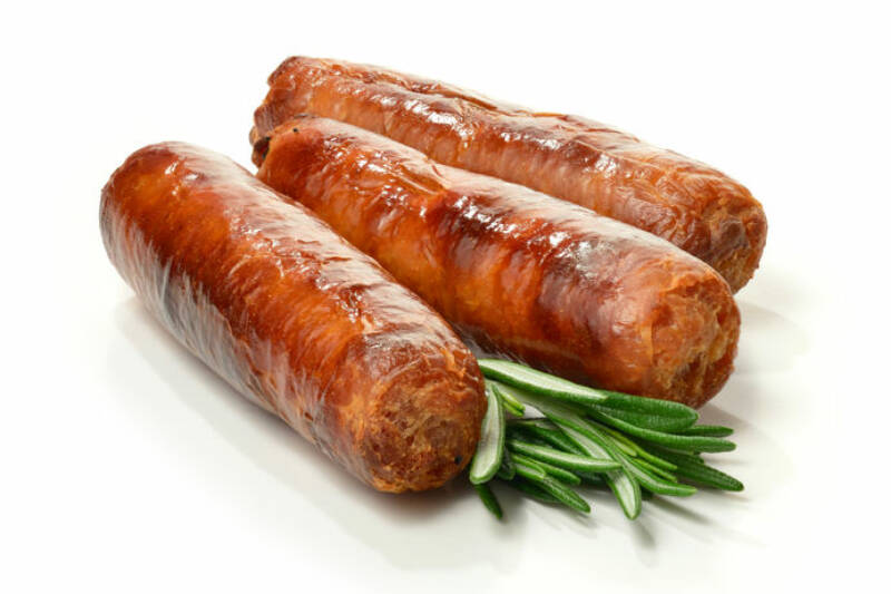 Studio close up of pin sharp focus grilled pork sausages stacked against a white surface with rosemary sprigs and soft shadows. Copy space.