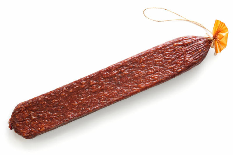 Premium stick of salami with string isolated on white.